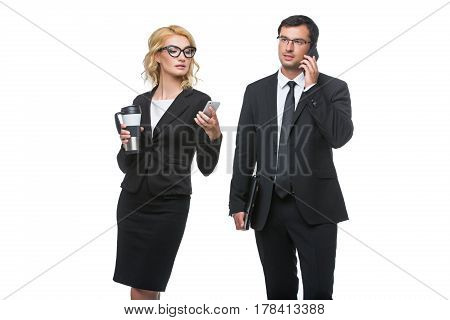 Beautiful business lady in glasses with coffee and handsome businessman holding leather folder and talking on mobile phone. Couple standing isolated on white background. Copy space.