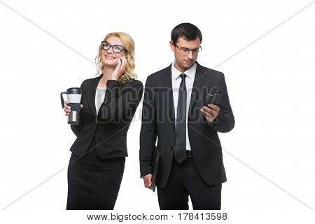 Beautiful business lady in glasses with coffee and handsome businessman holding leather folder talking on mobile phone. Couple standing isolated on white background. Copy space.