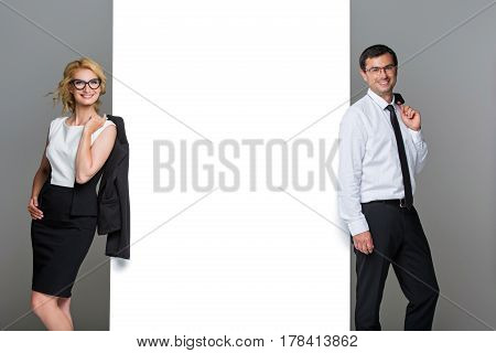 Beautiful business lady and handsome businessman standing near big empty poster. Happy expression. On gery background. Copy space.