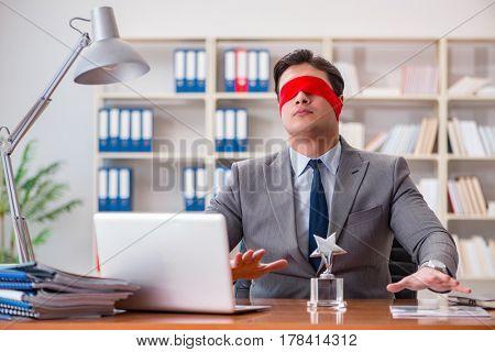 Blindfold businessman sitting at desk in office