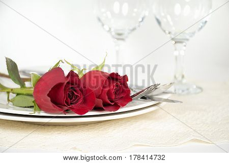 red roses and silverware on dinner plate with stemware and lace doily