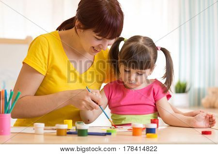cute mother teaching her daughter kid to paint