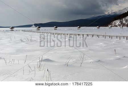 Snow-covered arbors on the shore of the winter lake Baikal
