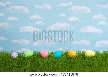 Colorful Easter Eggs lined up in a row on tall grass with blue background sky with clouds. Copy space