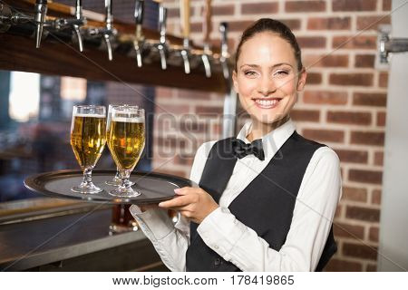 Beautiful barmaid serving three beers