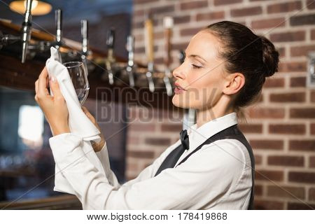 Beautiful barmaid cleaning a glass with a towel