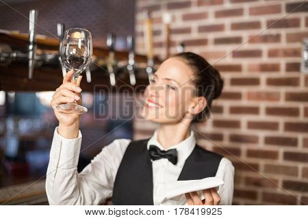 Beautiful barmaid looking at a shiny wine glass
