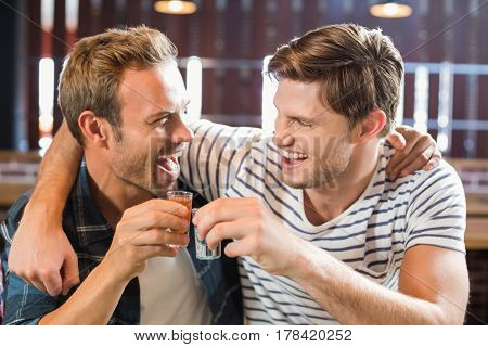 Men toasting with shots while looking at each other