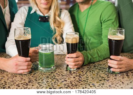 Men holding normal beers while woman holds green beer