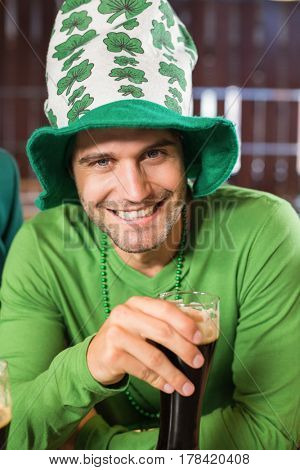 Smiling man with a hat toasting a beer in a bar