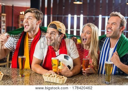 Friends watching a game on tv in a bar