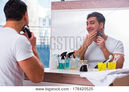 Young handsome man shaving in the morning
