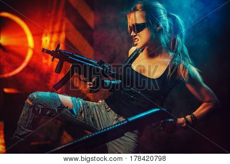 Young strong woman warrior with big guns in dramatic urban night scene