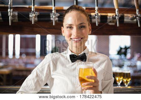 Beautiful barmaid a beer at a bar
