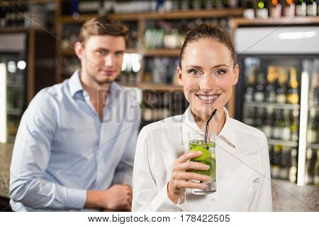 Beautiful woman drinking beverage in a bar in front of man