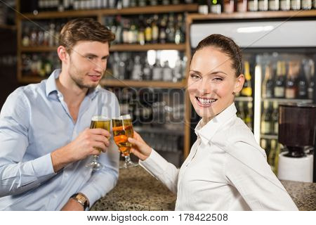 Attractive man and barmaid toasting with beers with barmaid looking at camera