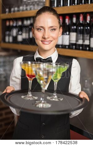 Beautiful barmaid serving cocktails in a bar