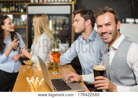 Handsome men working on laptop while women talk behind at the bar