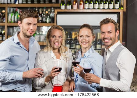 Attractive friends toasting with red wine in a bar