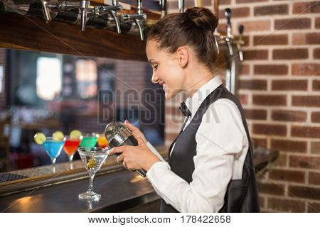 Beautiful barmaid pouring a cocktail in a bar