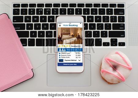 white pink phone with app hotel booking screen on notebook keyboard
