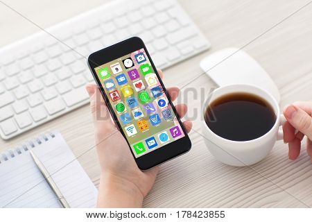woman hands holding coffee white phone with home screen icons apps and keyboard