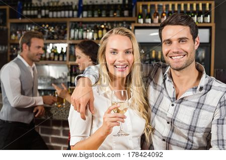 Attractive couple smiling at camera with woman holding white wine