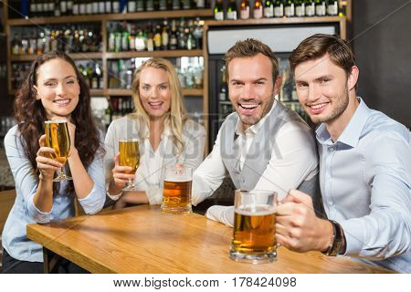 Attractive friends smiling at camera and toasting beers