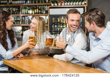 Women looking at one another and men looking at one another toasting