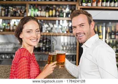 Attractive couple smiling at camera and toasting with beer