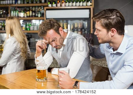 Tired man holding head in hand in a bar