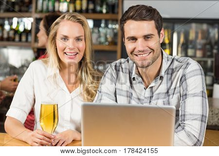 Attractive couple smiling at camera in a bar