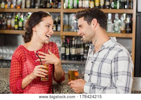 Attractive couple facing each other with beers in hand