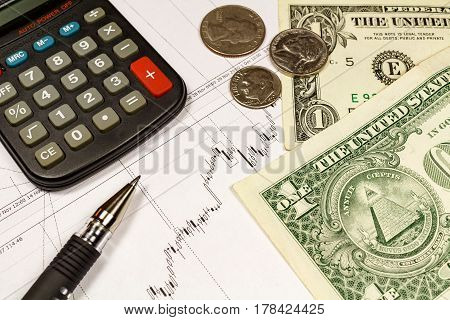 Electronic calculator coins with US dollars banknotes and ball pen on the background of currency growth schedule