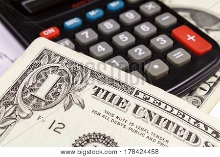 US dollars banknotes lying on the surface of the electronic calculator. Focus in the banknote