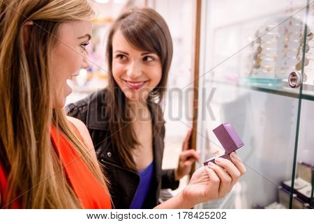 Two beautiful women selecting a finger ring from display in jeweler shop
