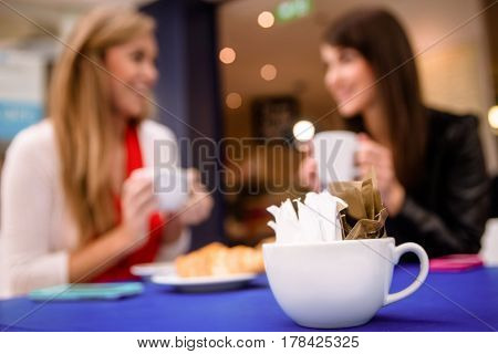 Packets of sugar in a cup and women having coffee and talking in background