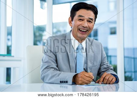 Happy businessman on his desk in office