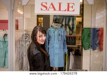 Portrait of beautiful woman window shopping in front of sale window