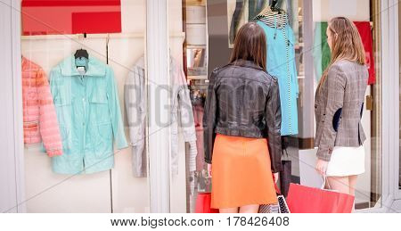 Two rear women with shopping bags window shopping in mall