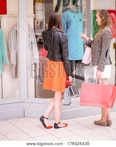Two beautiful women with shopping bags window shopping in mall