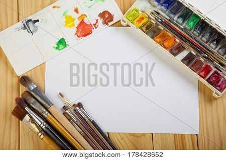 Paint Brushes And Empty White  Paper On A Wooden Table