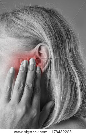 Woman with earache ear pain closeup black and white photo with red spots