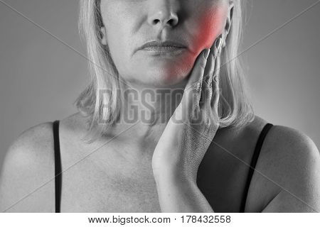 Aged woman with toothache teeth pain closeup black and white photo with red spots