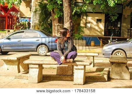 Caracas,Venezuela-January 14,2011: A woman sits on a bench on a public square while listening to music