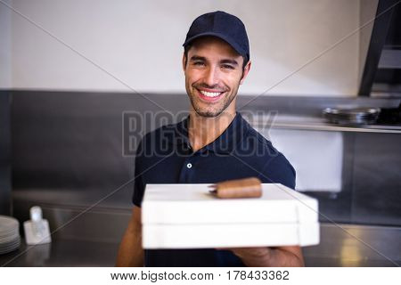 Pizza delivery man showing box in commercial kitchen