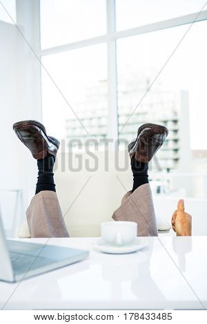 Businessman lying on the ground with feet up and thumps up