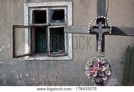 Wooden cross with crucifixion against the background of an old ruined house