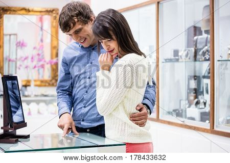 Happy couple looking at display while shopping in mall