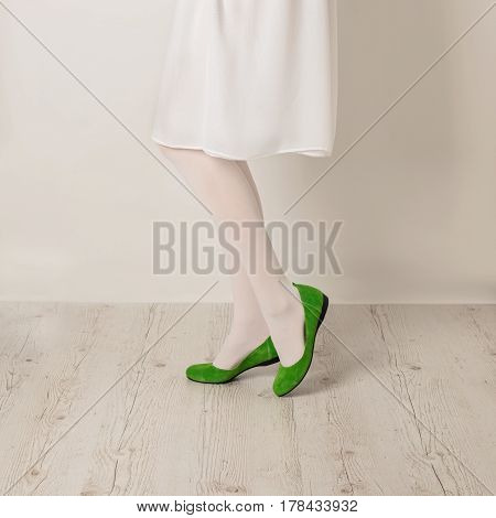 Female legs in white tights skirt and ballet flats on a white background. Selective focus.